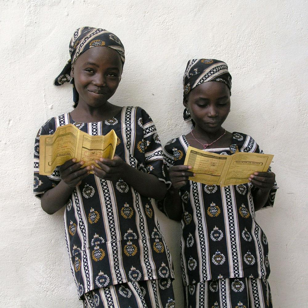 Zwei Schülerinnen zeigen stolz ihre Zeugnisse